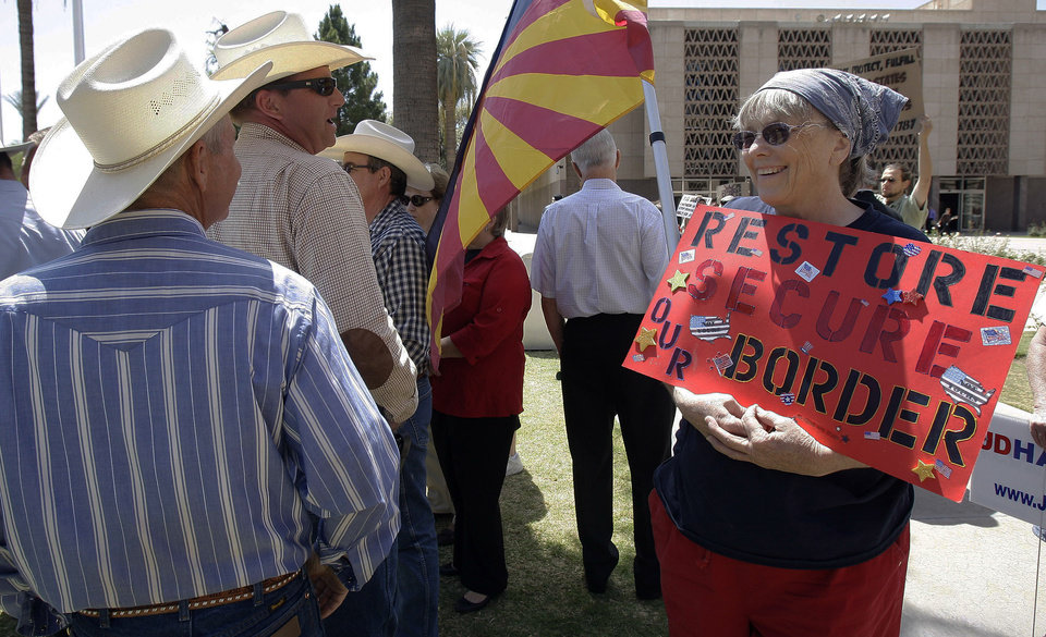 Photo - FILE - In this April 13, 2010 file photo, Ginger Niesen, right, talks with ranchers John Ladd, left, and Ban Bell as they join other ranchers, state legislators and protestors at the Arizona Capitol in Phoenix following the shooting death of Arizona rancher Robert Krentz. Krentz was gunned down while checking water lines on his property near the border where ranchers scoff at the word