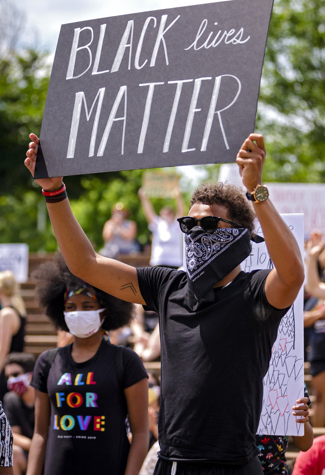 Photo - Norman native and Atlanta Hawk basketball player Trae Young, right, gathers with others protesters as they carry signs during a protest at Andrews Park on Monday, June 1, 2020, in Norman, Okla. in response to the death of George Floyd.  [Chris Landsberger/The Oklahoman]
