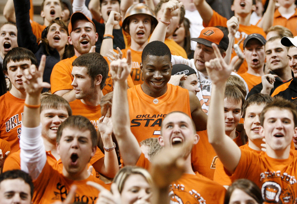 Photo - OSU's Obi Muonelo celebrates with students after OSU's win in the NCAA college basketball game between the Oklahoma State University and Texas A&M at Gallagher-Iba Arena in Stillwater, Okla., Wednesday, January 27, 2010. Photo by Bryan Terry, The Oklahoman