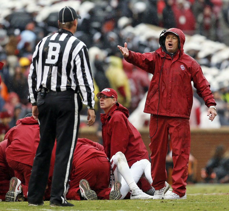 Photo - OU coach Bob Stoops talks to an official as medical staff help Dede Westbrook (11) in the second quarter during the Bedlam college football game between the Oklahoma Sooners (OU) and the Oklahoma State Cowboys (OSU) at Gaylord Family - Oklahoma Memorial Stadium in Norman, Okla., Saturday, Dec. 3, 2016. Photo by Nate Billings, The Oklahoman