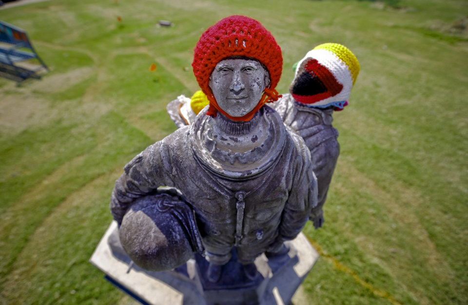 Photo - Knitted hats are attached to statues in the Enid town square as part of the Yarnover Enid community art event on Friday, Sept. 6, 2013 in Enid, Okla. The public art project was established to bring the town together to display 'art graffiti' created from items made and donated by the community.  Photo by Chris Landsberger, The Oklahoman