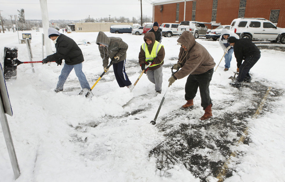 Church members work together to clear snow from the parking lot at the Ridgecrest  United Methodist Church in Oklahoma City, Saturday, Jan. 30, 2010. By Paul Hellstern, The Oklahoman