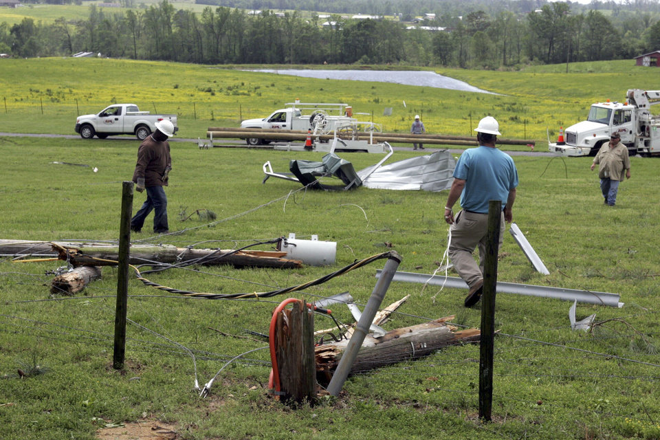 Photo - Utility crews work to repair the damage from near Arab, Ala.  after a storm early Wednesday,  April 27, 2011.   A wave of thunderstorms with near hurricane-force winds pushed across Alabama on Wednesday, killing at least five people including a woman in a mobile home and sending snapped tree limbs onto cars and homes. The widespread destruction caused Gov. Robert Bentley to declare a state of emergency by midday, saying tornadoes, severe thunderstorms, hail, and straight-line winds caused damage to