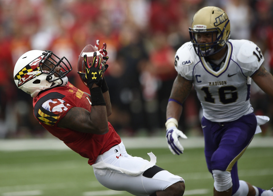 Photo - Maryland wide receiver Stefon Diggs, left, makes a catch against James Madison safety Dean Marlowe (16) during the first half of an NCAA college football game, Saturday, Aug. 30, 2014, in College Park, Md. (AP Photo/Nick Wass)