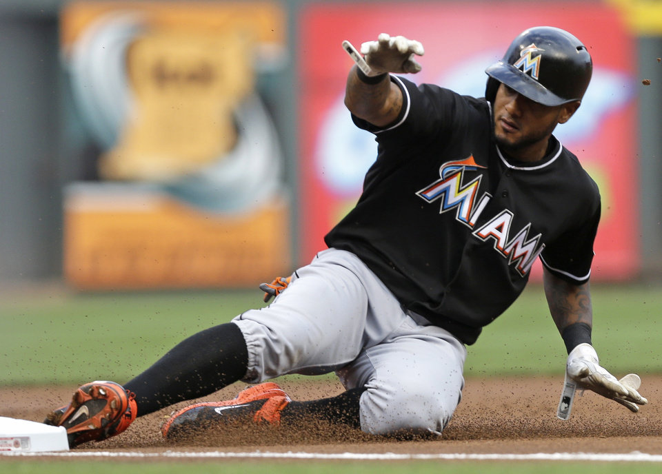 Photo - Miami Marlins' Jordany Valdespin advances to third on a fly-out by Casey McGehee in the first inning of a baseball game against the Cincinnati Reds, Friday, Aug. 8, 2014, in Cincinnati. (AP Photo/Al Behrman)