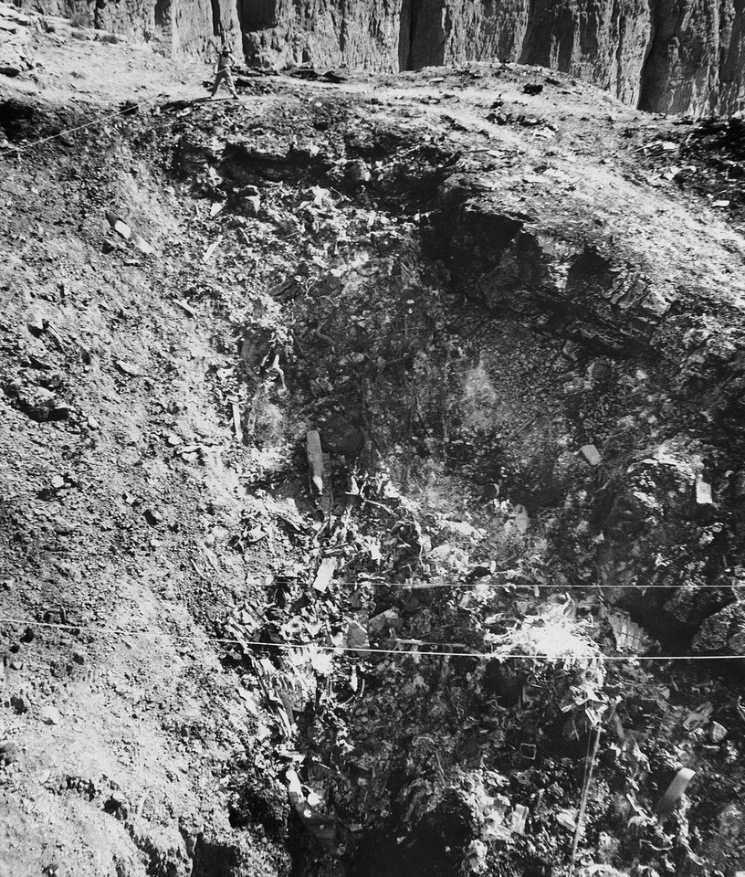 Photo - FILE - In this July 7, 1956 file photo, Anton Spinas, leader of Swiss climbers, top, tests ropes strung across steep chasm where wreckage of United Airlines UAL DC-7 lays strewn in Grand Canyon. On Tuesday, July 8, 2014, the Grand Canyon National Park will mark the designation of the crash site as a National Historic Landmark in a ceremony overlooking the gorge where the wreckage was scattered over 1.5 square miles. (AP Photo/Pool, File)