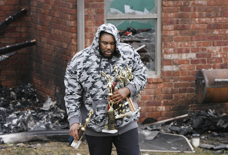 Photo - A man carries trophies from the burned house of Nathan and Sammetra Christman as he helps salvage personal belongings from the home at 2040  Westbury St. in the Oakwood East Royale neighborhood.The home  was destroyed in Thursday's wildfires. Photo by Jim Beckel, The Oklahoman