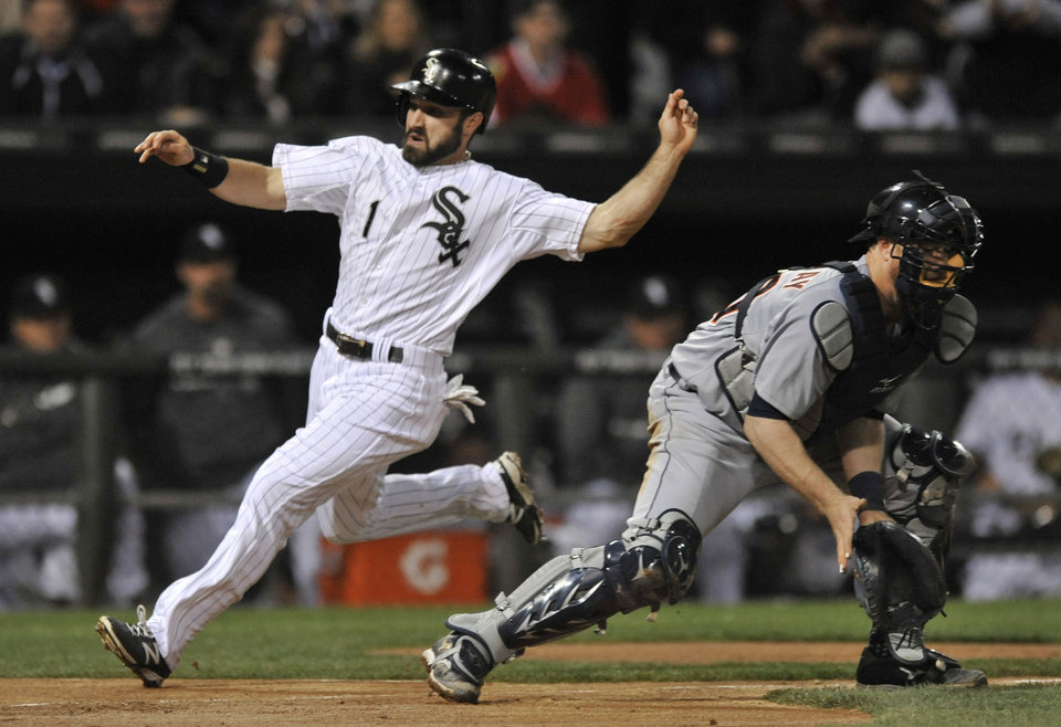 Photo - Chicago White Sox's Adam Eaton (1), crosses home plate safely as Detroit Tigers catcher Bryan Holaday waits for the throw during the third inning of a baseball game, Tuesday, April 29, 2014, in Chicago. (AP Photo/Paul Beaty)