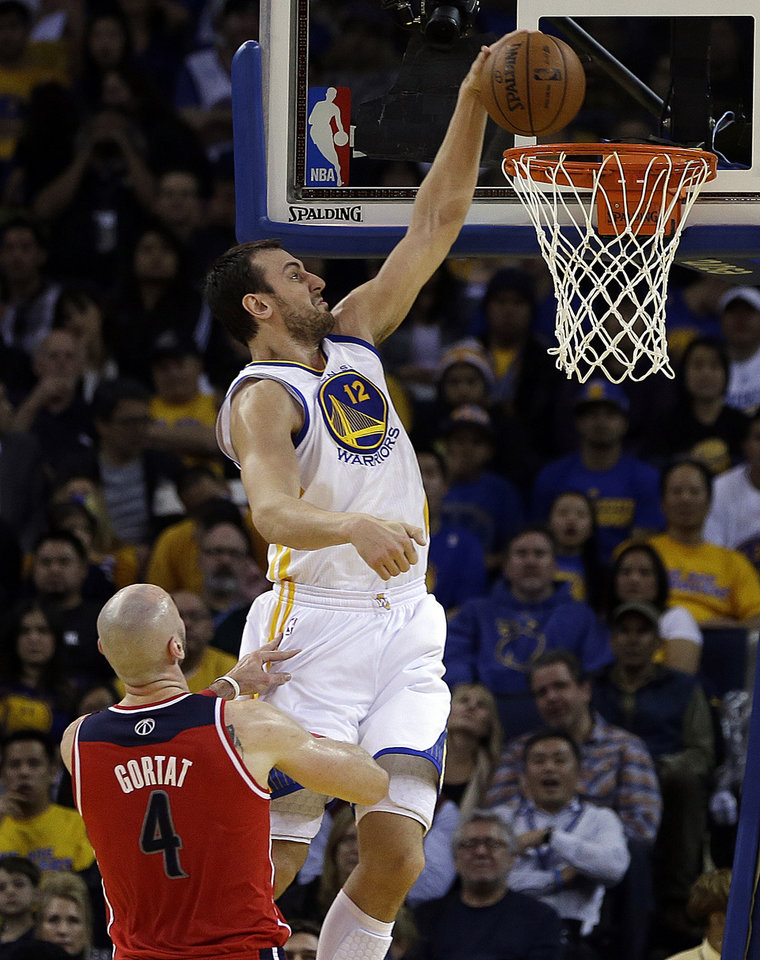 Photo - Golden State Warriors' Andrew Bogut (12) scores past Washington Wizards' Marcin Gortat (4) during the first half of an NBA basketball game, Tuesday, Jan. 28, 2014, in Oakland, Calif. (AP Photo/Ben Margot)