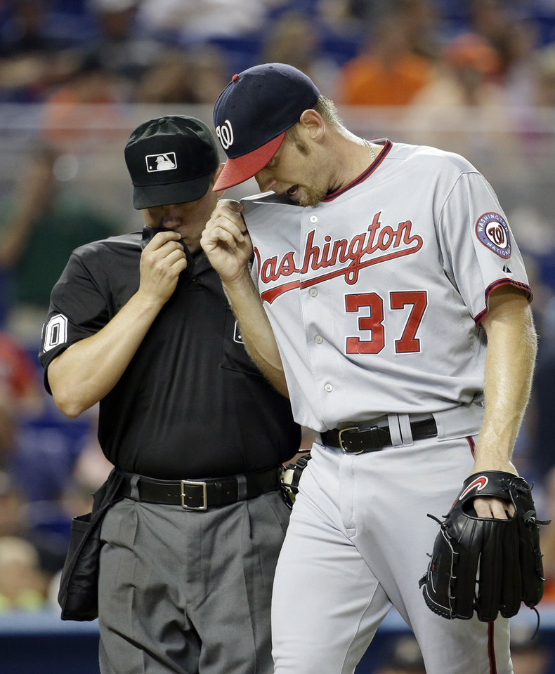 Photo - Washington Nationals starting pitcher Stephen Strasburg (37) talks with home plate umpire D.J. Reyburn, left, after pitching in the third inning during a baseball game, Tuesday, July 29, 2014, in Miami. (AP Photo/Lynne Sladky)