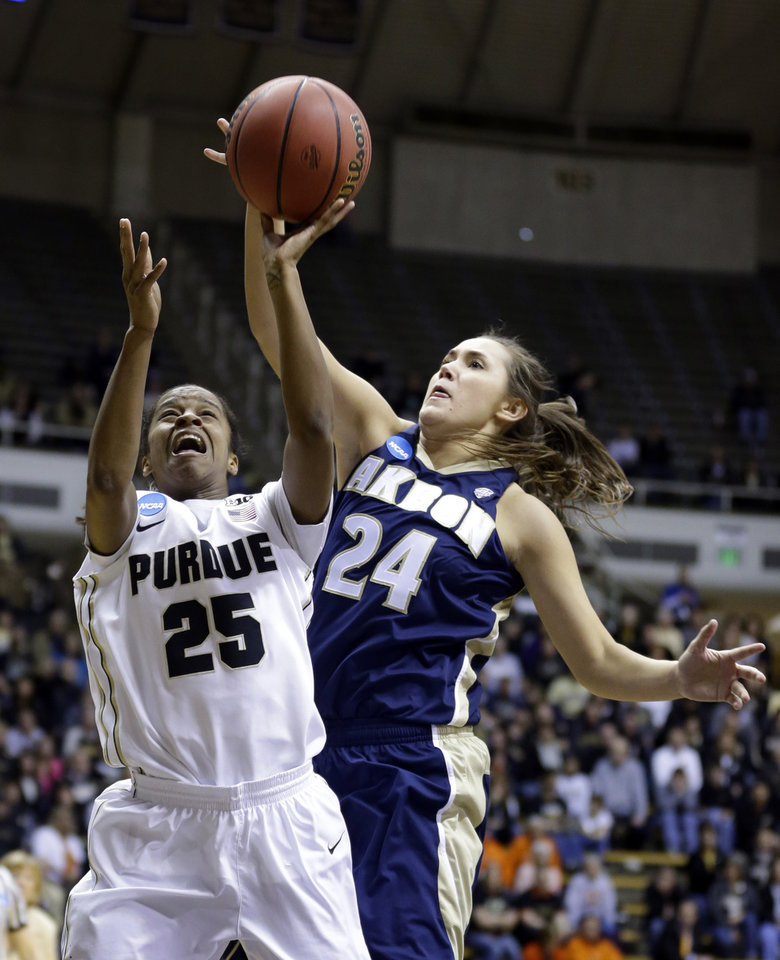 Photo - Akron forward Sina King comes from behind to block the shot of Purdue guard April Wilson during the second half of a first-round game in the NCAA women's college basketball tournament in West Lafayette, Ind., Saturday, March 22, 2014. Purdue defeated Akron 84-55. (AP Photo/Michael Conroy)