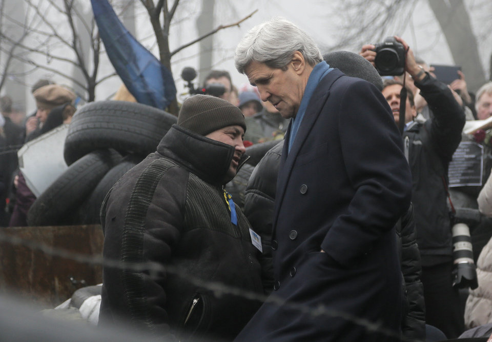 Photo - U.S. Secretary of State John Kerry, right, inspects protesters barricades in Kiev, Ukraine, Tuesday, March, 4, 2014. In a somber show of U.S. support for Ukraine's new leadership, Secretary of State John Kerry walked the streets Tuesday where nearly 100 anti-government protesters were gunned down by police last month, and promised beseeching crowds that American aid is on the way.  The Obama administration announced a $1 billion energy subsidy package in Washington as Kerry was arriving in Kiev.(AP Photo/Efrem Lukatsky)