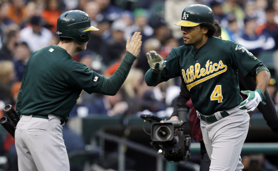 Oakland Athletics' Coco Crisp is congratulated after hitting a solo home run during the first inning of Game 1 of the American League division baseball series against the Detroit Tigers, Saturday, Oct. 6, 2012, in Detroit. (AP Photo/Paul Sancya)