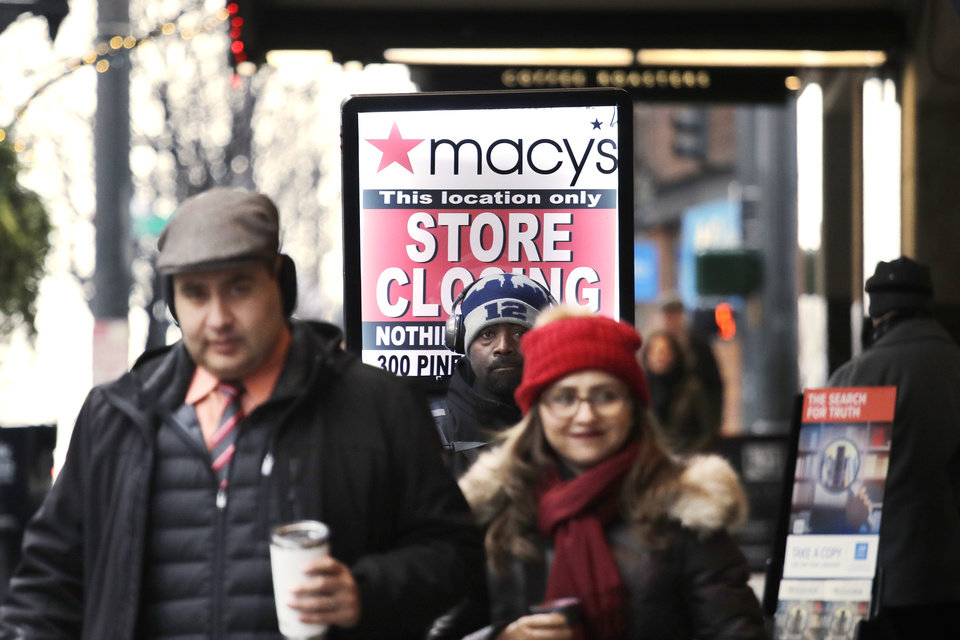 "Photo - In this photo taken Thursday, Jan. 9, 2020, Raymond Martin, center, walks with a ""store closing"" sign on his back in front of the Macy's store in downtown Seattle. The store is one of nearly 30 Macy's stores to be closed nationwide in the coming weeks. (AP Photo/Elaine Thompson)"