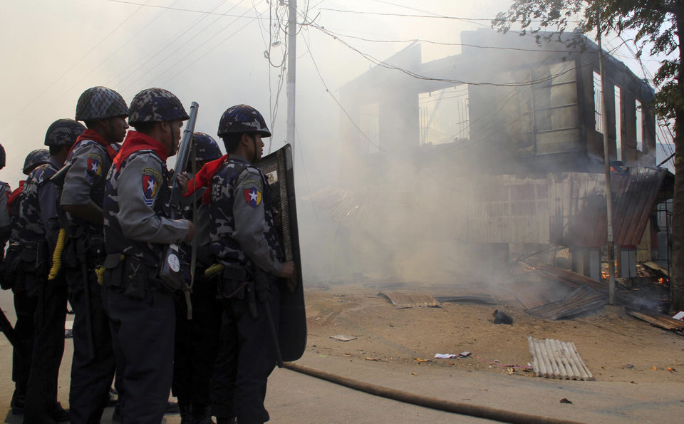 In this Thursday, March. 21, 2013 photo, armed Myanmar police oficers provide security around a smoldering building following ethnic unrest between Buddhists and Muslims in Meikhtila, Mandalay division, about 550 kilometers (340 miles) north of Yangon, Myanmar. Burning fires from two days of Buddhist-Muslim violence that killed at least 20 people smoldered across a central Myanmar town Friday as residents cowered indoors amid growing fears the country\'s latest bout of sectarian bloodshed could spread. The government\'s struggle to contain the unrest in Meikhtila is proving another major challenge President Thein Sein\'s reformist administration as it attempts to chart a path to democracy after nearly half a century of military rule that once crushed all dissent. (AP Photo)