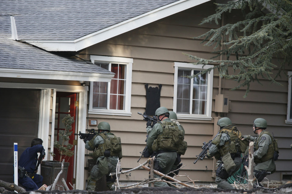 Photo - A SWAT team enters a home in Big Bear, Calif. in search of shooting suspect Christopher Dorner, Thursday, Feb. 7, 2013. Thousands of police officers hunted Thursday for one of their own: a former Los Angeles officer angry over his firing and sought in a deadly shooting rampage after warning he would wage
