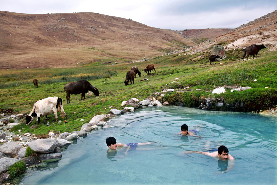 Photo - In this Sept. 13, 2013 photo, Iranians bathe at a hot mineral water spring on the slopes of Iran's Sabalan mountain, in the northwestern town of Sarein. According to local media reports the region welcomes more than eight million tourists annually, who flock to its many swimming pools, hotels and restaurants. Others bathe in outdoor natural springs on grassy hillsides as animals graze in the background. (AP Photo/Ebrahim Noroozi)