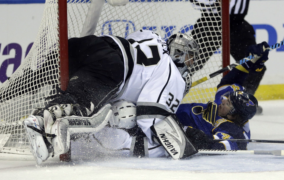 Photo - St. Louis Blues' T.J. Oshie, right, slides into the goal past Los Angeles Kings goalie Jonathan Quick, top left, after being taken down by Kings' Jake Muzzin during the second period of an NHL hockey game, Thursday, Jan. 16, 2014, in St. Louis. Oshie was awarded a penalty shot and scored following the play. (AP Photo/Jeff Roberson)