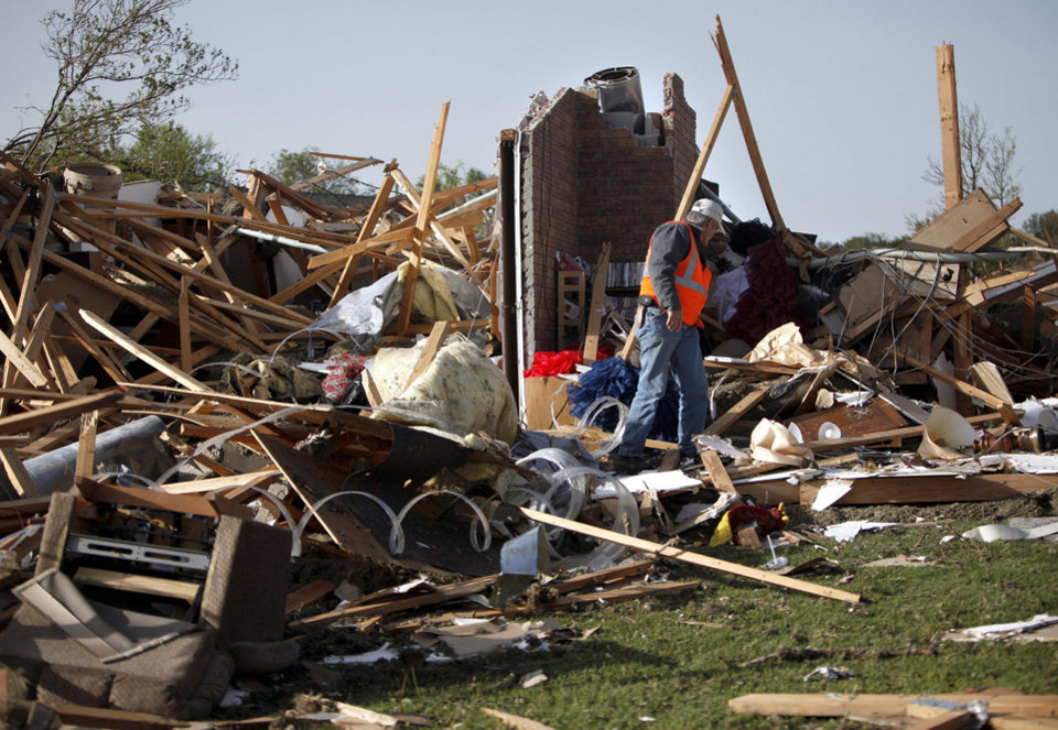 Photo - An official looks over damage, Sunday, April 15, 2012.  A tornado struck Woodward early Sunday morning. Photo by Sarah Phipps, The Oklahoman.