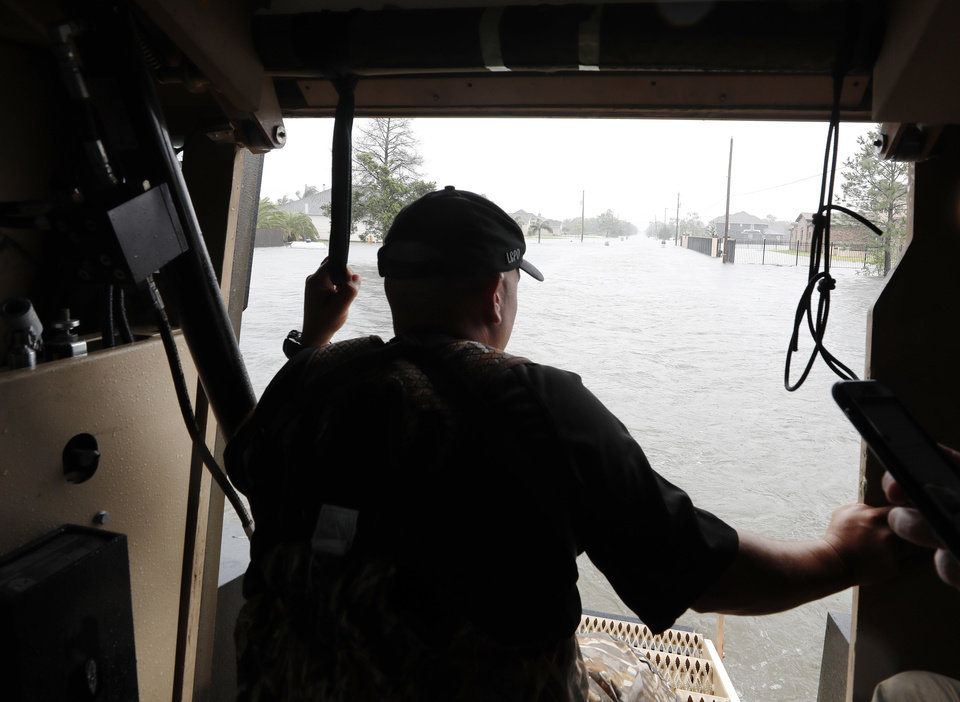Photo - League City Police Officer Matt Maggiolino surveys the flooding from Tropical Storm Harvey in League City, Texas while checking on the welfare of residents on Tuesday, Aug. 29, 2017. (Kevin M. Cox/The Galveston County Daily News via AP)