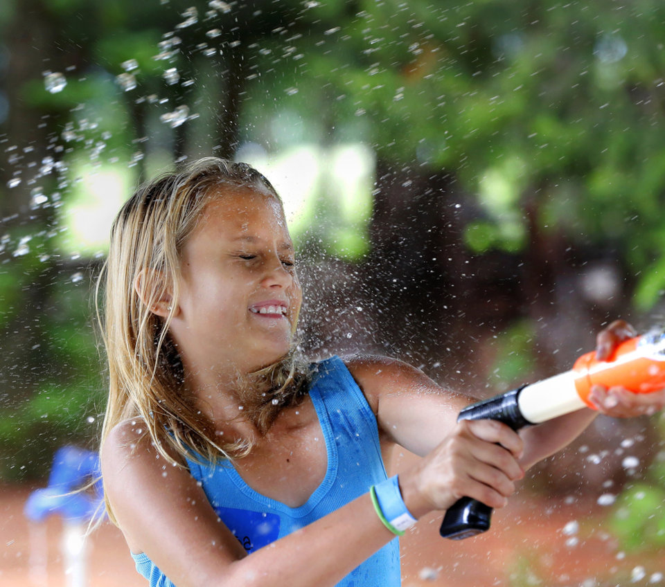 Photo -  A girl braces herself against being hit at the water gun station during an event hostd by Redeeming the Family. Photo by Jim Beckel, The Oklahoman   Jim Beckel -  THE OKLAHOMAN