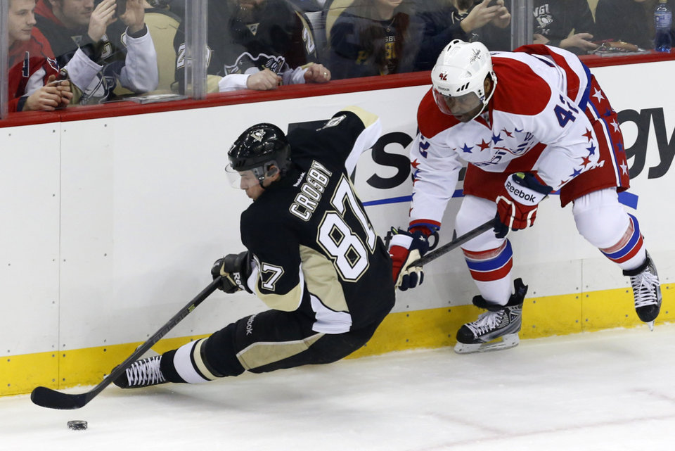Photo - Washington Capitals' Joel Ward (42) trips Pittsburgh Penguins' Sidney Crosby (87) during the first period of an NHL hockey game in Pittsburgh, Wednesday, Jan. 15, 2014. (AP Photo/Gene J. Puskar)