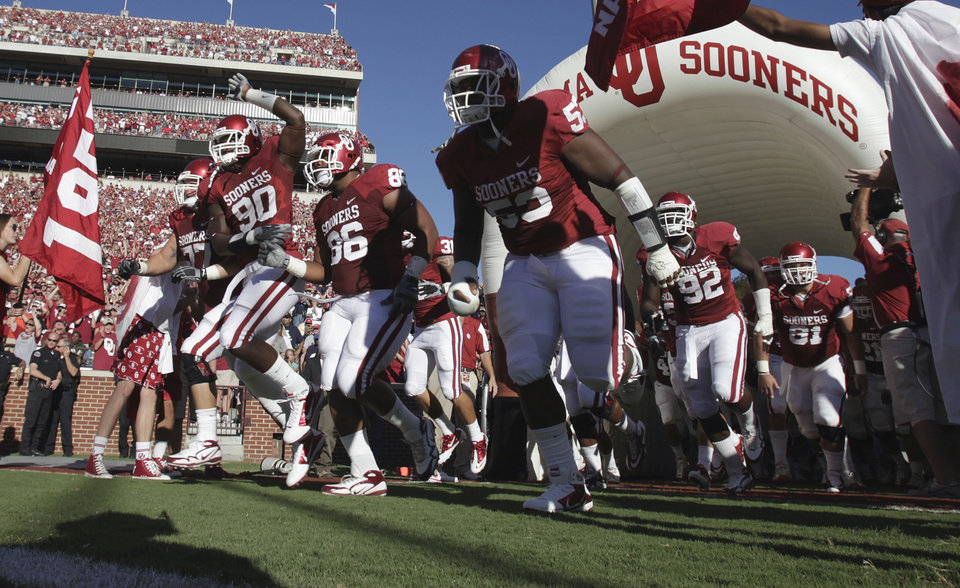 Photo - Players David King (90), Adrian Taylor (86) and Casey Walker (53) take the field for the college football game between the University of Oklahoma Sooners (OU) and Utah State University Aggies (USU) at the Gaylord Family-Oklahoma Memorial Stadium on Saturday, Sept. 4, 2010, in Norman, Okla.   Photo by Steve Sisney, The Oklahoman