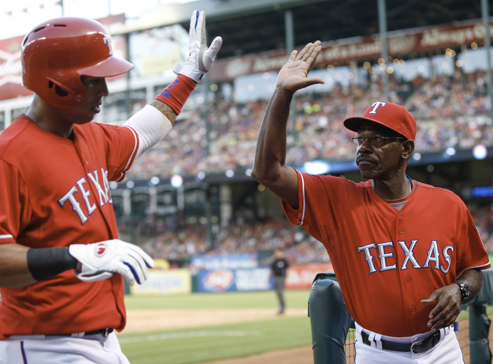 Photo - Texas Rangers manager Ron Washington, right, congratulates player Leonys Martin after his run against the Los Angeles Angels during the sixth inning of a baseball game, Monday, July 29, 2013, in Arlington, Texas. (AP Photo/Jim Cowsert)