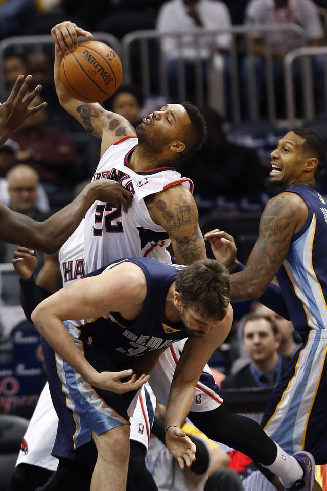 Photo - Atlanta Hawks forward Mike Scott (32) fouls Memphis Grizzlies center Marc Gasol (33) as he fights for a rebound against Gasol and forward James Johnson, right, during the first half of an NBA basketball game Saturday, Feb. 8, 2014, in Atlanta.  (AP Photo/John Bazemore)