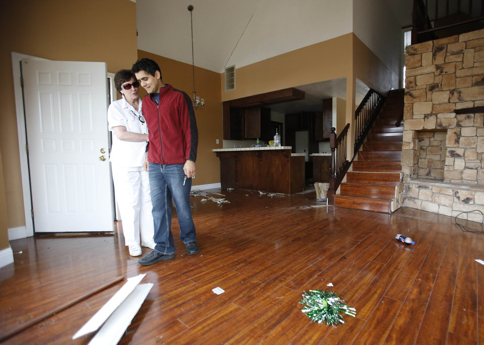 In this photo taken Monday, May 6 2013,  Jagtar Singh is comforted by his neighbor Blanka Doren, in the living room of his home he was forced to vacate when the hill it sits on began to sink in Lakeport, Calif.  Doren, 72,  whose home shares a wall with Singh's, was also forced to move from her home.  Officials believe that water that has bubbled to the surface is playing a role in the collapse of the hillside subdivision that has forced the evacuation of 10 homes and the notice of imminent evacuation of another 10 in this upscale subdivision.(AP Photo/Rich Pedroncelli)