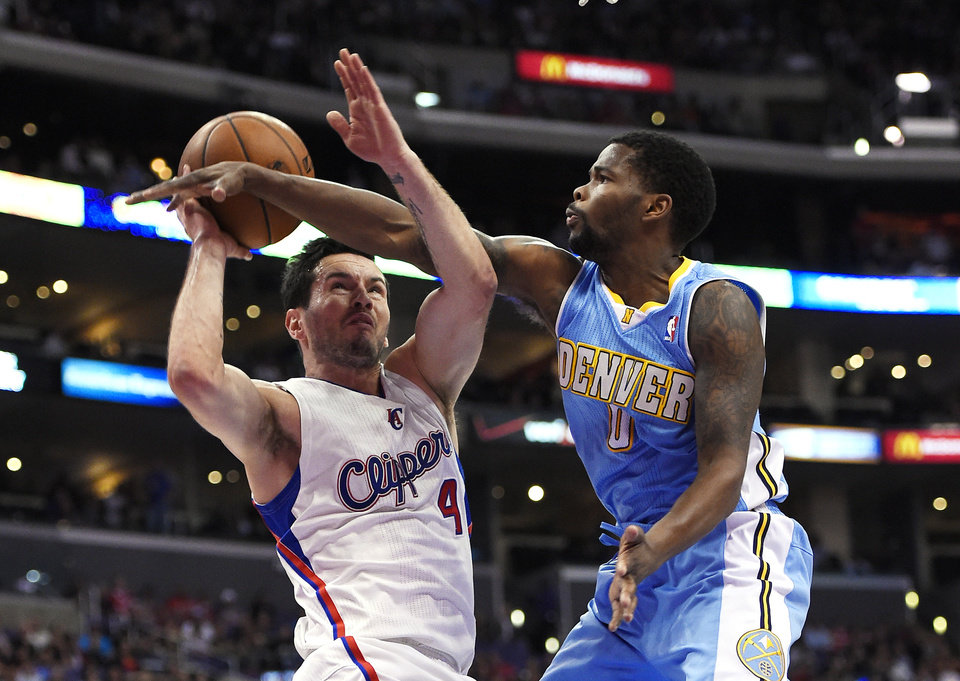Photo - Los Angeles Clippers guard J.J. Redick, left, looks to shoot as Denver Nuggets guard Aaron Brooks defends during the first half of an NBA basketball game, Tuesday, April 15, 2014, in Los Angeles.  (AP Photo/Mark J. Terrill)