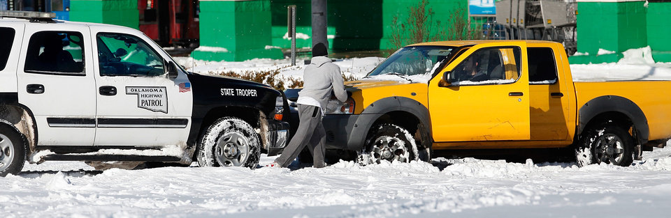 Photo - Oklahoma Highway Patrol Trooper Mike Roe pushes a motorist out of snow in a Midwest City parking lot. Many spent Christmas Day, Dc. 25, 2009,  digging out from record snow storm that dumped 14 inches of severe winter storm in the Oklahoma City area.   Photo by Jim Beckel, The Oklahoman