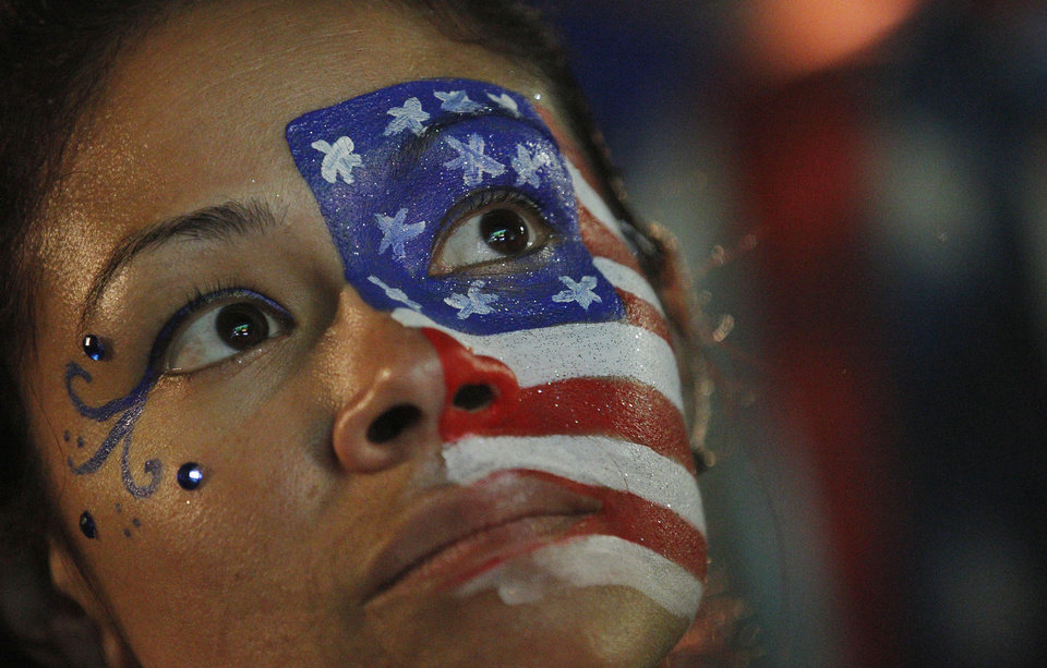 Photo - A fan of the U.S. national soccer team, with her face painted with the nation's colors watches her team's World Cup round of 16 match against Belgium on a live telecast inside the FIFA Fan Fest area on Copacabana beach in Rio de Janeiro, Brazil, Tuesday, July 1, 2014. Belgium beat the United States 2-1 in extra time to reach World Cup quarterfinals. (AP Photo/Leo Correa)