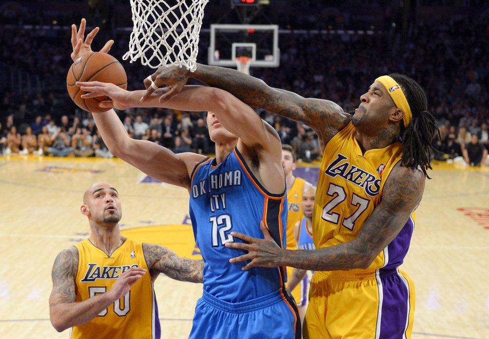 Photo -  Los Angeles Lakers forward Jordan Hill, right, blocks a shot by Oklahoma City Thunder center Steven Adams, center, of New Zealand, as center Robert Sacre stands near during the first half of an NBA basketball game Thursday, Feb. 13, 2014, in Los Angeles. (AP Photo/Mark J. Terrill)