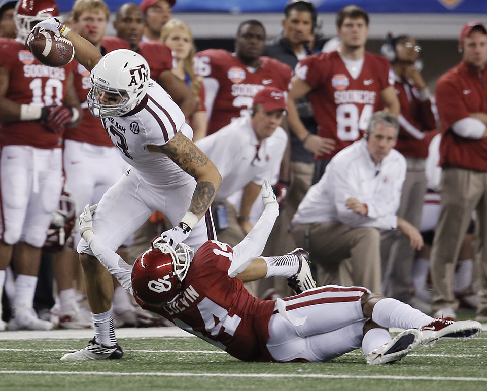 Photo - Texas A&M's Mike Evans (13) pushes off of Oklahoma's Aaron Colvin (14) during the college football Cotton Bowl game between the University of Oklahoma Sooners (OU) and Texas A&M University Aggies (TXAM) at Cowboy's Stadium on Friday Jan. 4, 2013, in Arlington, Tx. Photo by Chris Landsberger, The Oklahoman