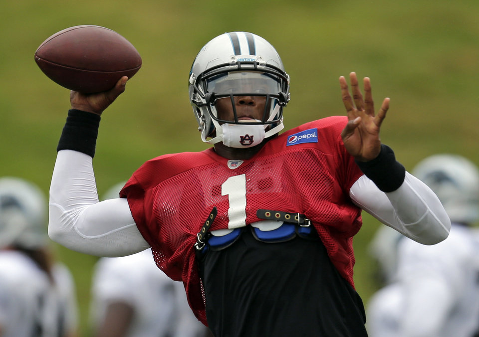 Photo - Carolina Panthers quarterback Cam Newton (1) throws a pass during an NFL football training camp practice in Spartanburg, S.C., Tuesday, July 30, 2013. (AP Photo/Chuck Burton)