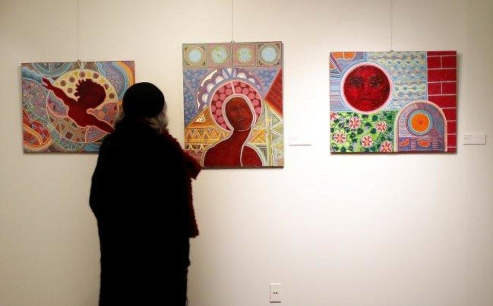 Photo - A visitor looks at artwork by Edward Grady during the Feb. 13 opening reception of