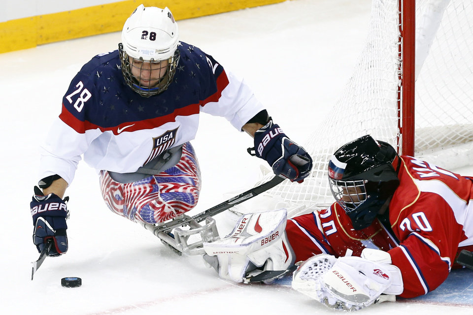 Photo - United States's Paul Schaus, left in action with Russia's Vladimir Kamantcev, right during the gold medal ice sledge hockey match between United States and Russia at the 2014 Winter Paralympics in Sochi, Russia, Saturday, March 15, 2014. (AP Photo/Pavel Golovkin)
