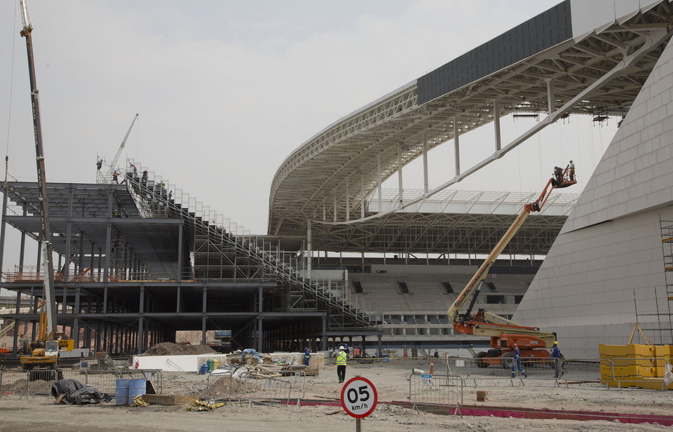 Photo - Men work at the Itaquerao stadium in Sao Paulo, Brazil, Wednesday, April 9, 2014. The stadium which remains under construction is slated to host the World Cup opener match between Brazil and Croatia on June 12. About 20,000 temporary seats are being installed behind the goals to increase the stadium's capacity to nearly 70,000. (AP Photo/Andre Penner)
