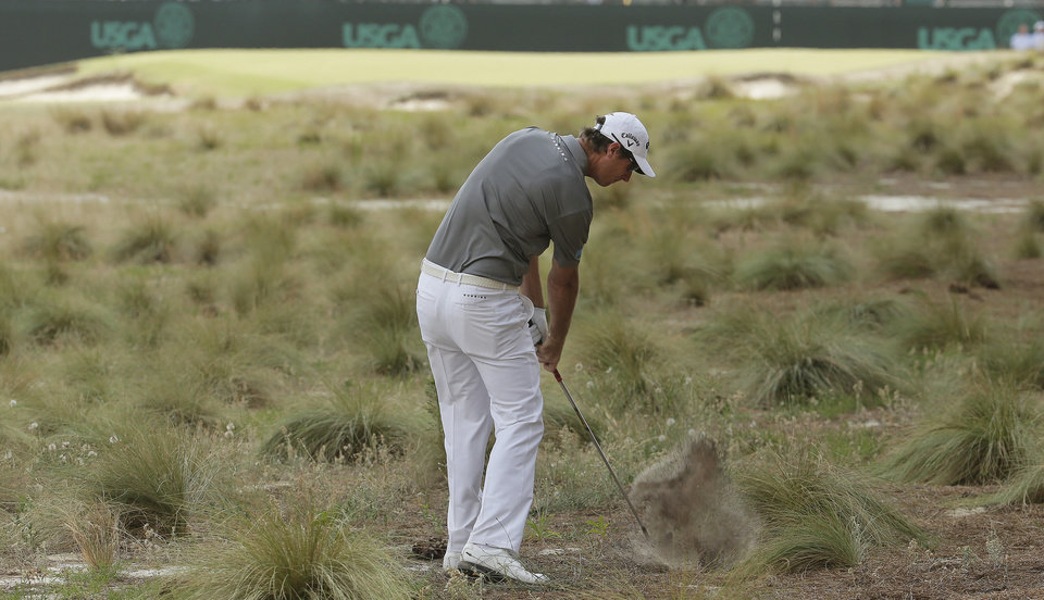 Photo - Nicolas Colsaerts, of Belgium, hits out of the native area on the 11th hole during the first round of the U.S. Open golf tournament in Pinehurst, N.C., Thursday, June 12, 2014. (AP Photo/Charlie Riedel)
