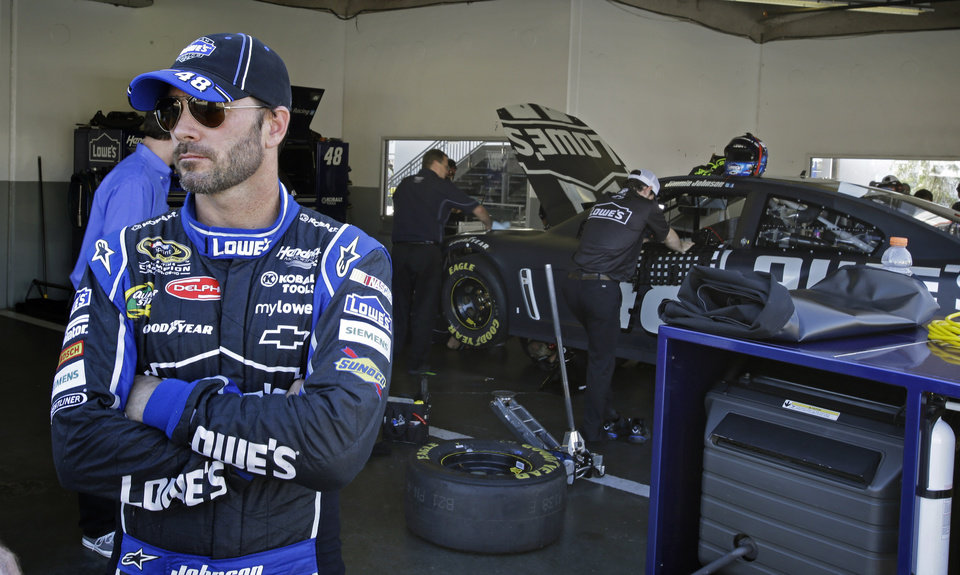 Driver Jimmie Johnson waits in his garage while crew members make adjustments to his car during NASCAR auto race testing at Daytona International Speedway, Thursday, Jan. 10, 2013, in Daytona Beach, Fla. (AP Photo/John Raoux)