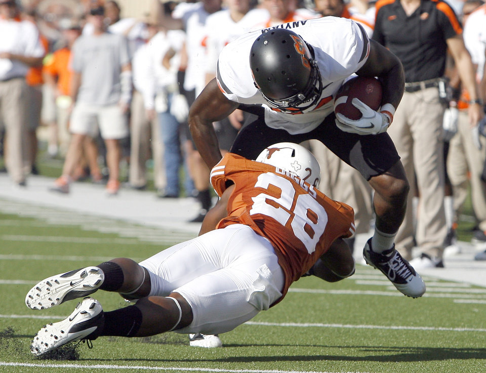 Oklahoma State\'s Hubert Anyiam (84) is tackled by Texas\' Malcolm Brown (28) during second half of a college football game between the Oklahoma State University Cowboys (OSU) and the University of Texas Longhorns (UT) at Darrell K Royal-Texas Memorial Stadium in Austin, Texas, Saturday, Oct. 15, 2011. Photo by Sarah Phipps, The Oklahoman