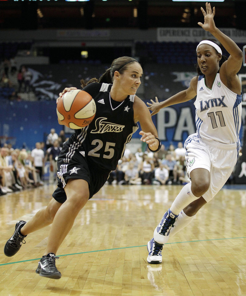 """Photo - File- This Aug. 4, 2011 file photo shows San Antonio Silver Stars guard Becky Hammon, left, driving past Minnesota Lynx guard Candice Wiggins in the first half of a WNBA basketball game in Minneapolis. Hammon's return from injury is critical to the team's fortunes. Entering her 16th season, she has career averages of 13.3 points and 3.8 assists. """"Becky makes things work,"""" coach Dan Hughes said. """"She's veteran enough to understand not only her position, but the totality of what we're doing. She can communicate it on the floor in a way that provides understanding and that's what your great players do."""" (AP Photo/Stacy Bengs, File)"""