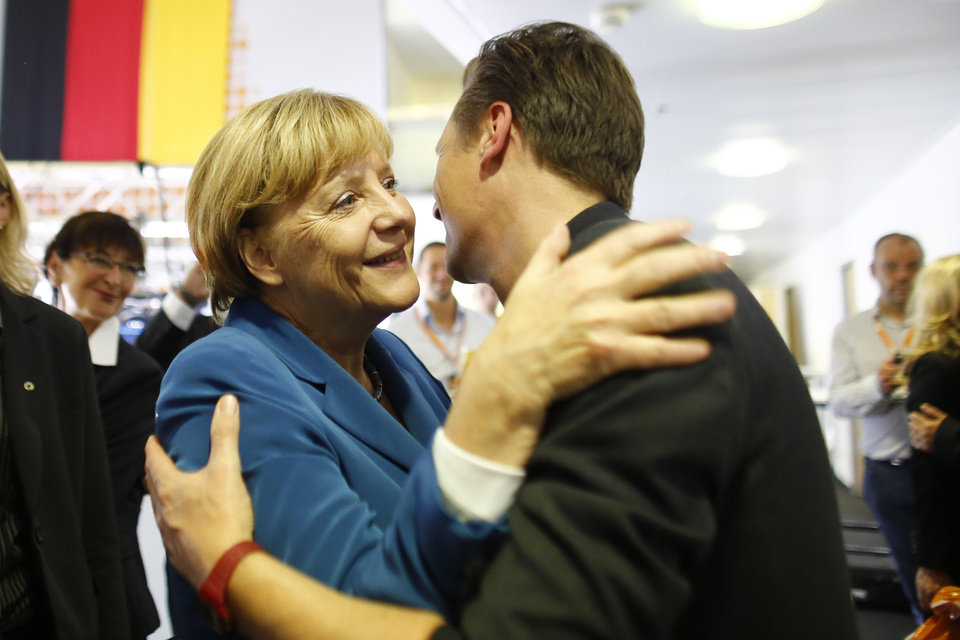 German Chancellor Angela Merkel, chairwoman of the Christian Democratic party, CDU, greets a supporter at the party headquarters after the national elections in Berlin Sunday, Sept. 22, 2013. Chancellor Angela Merkel\'s conservatives triumphed in Germany\'s election Sunday, and could even win the first single party majority in more than 50 years. Her center-right coalition partners risked ejection from parliament for the first time in their post-World War II history.(AP Photo/Markus Schreiber)