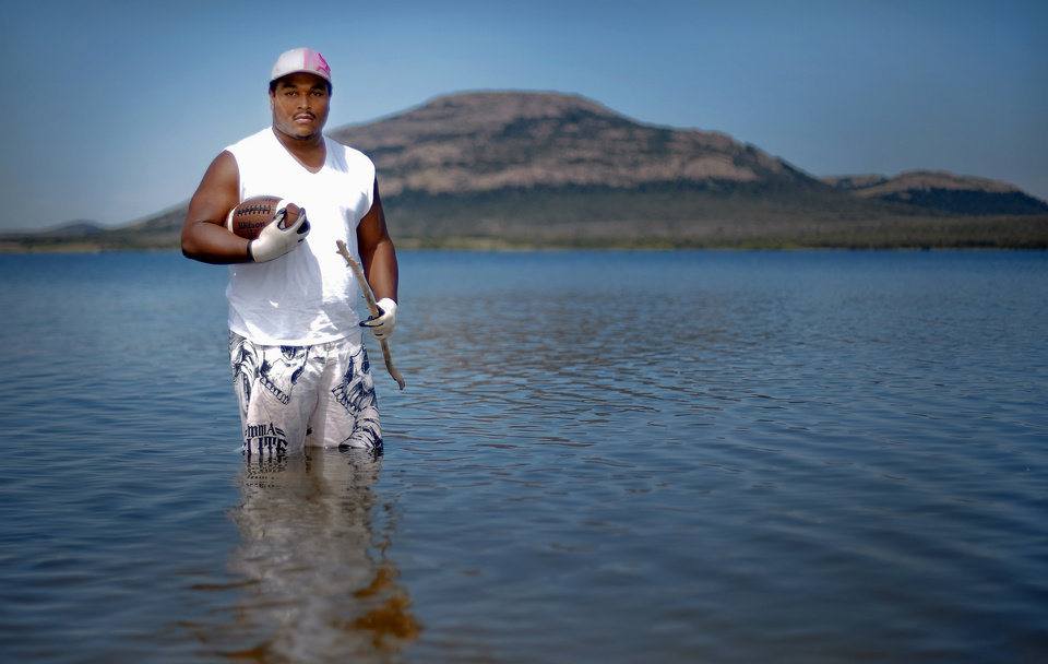 SUPER 30 / HIGH SCHOOL FOOTBALL PLAYER: Lawton High School's true country boy Ivan Thomas pose for a photo with his football and noodling stick in Lake Lawtonka on Tuesday, June 18, 2013 in Lawton, Okla.   Photo by Chris Landsberger, The Oklahoman