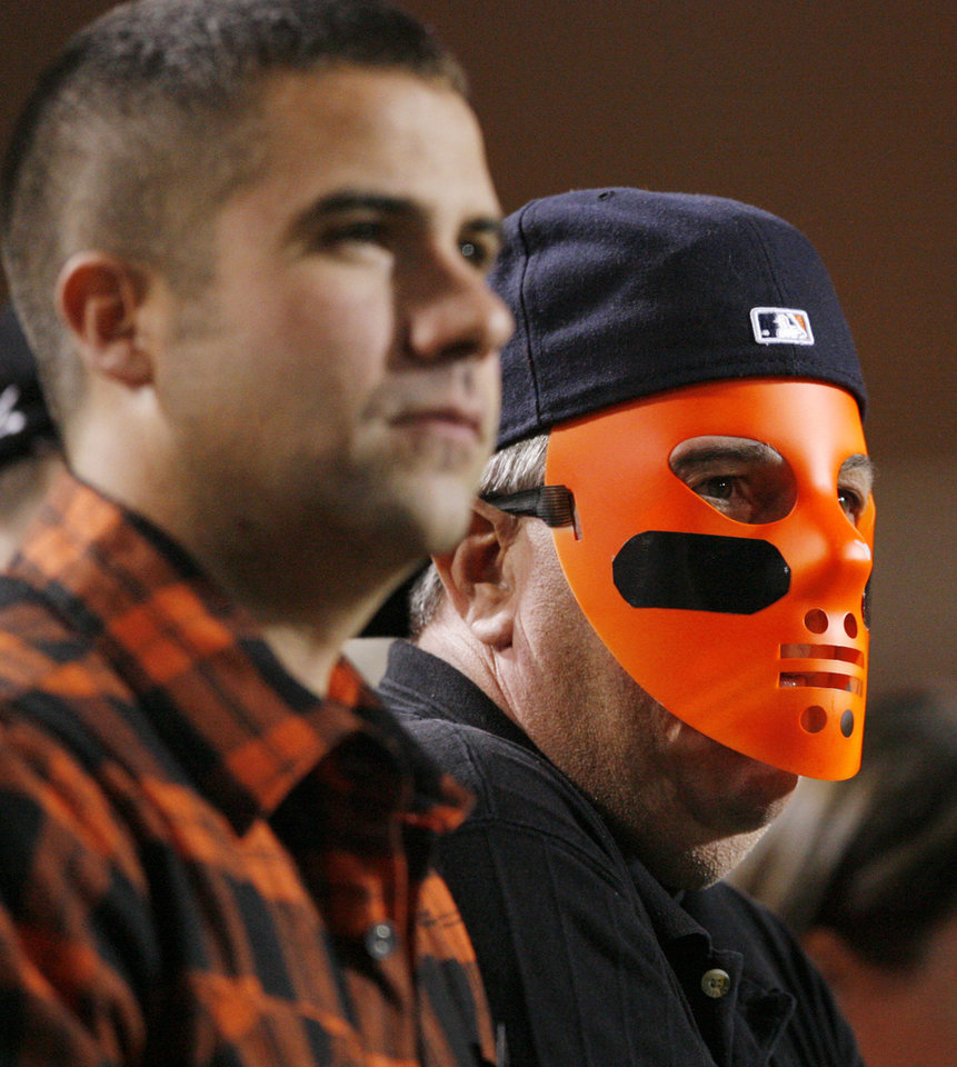 Photo - OSU fans Larry DeKinder, right, and his son Lucas DeKinder watch the college football game between the Oklahoma State University Cowboys (OSU) and the University of Texas Longhorns (UT) at Boone Pickens Stadium in Stillwater, Okla., Saturday, Oct. 31, 2009. Photo by Nate Billings, The Oklahoman