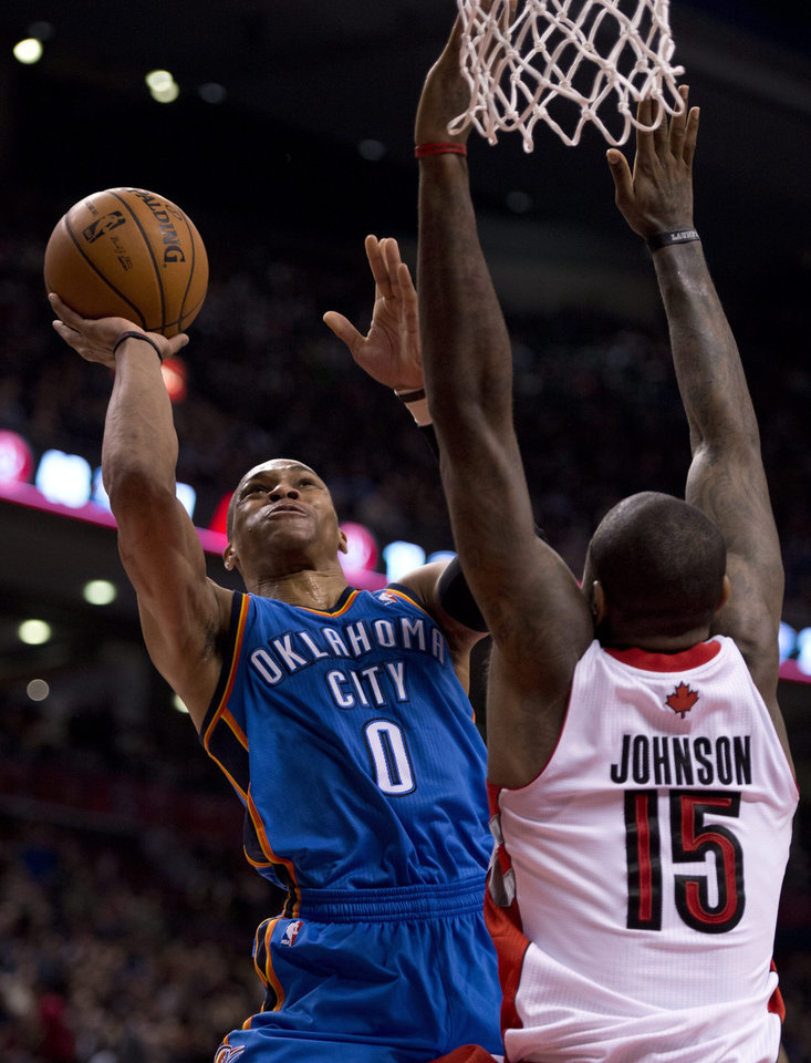 Oklahoma City Thunder guard Russell Westbrook (0) shoots against Toronto Raptors forward Amir Johnson (15) during first-half NBA basketball game action in Toronto, Sunday, Jan.6, 2013. (AP Photo/The Canadian Press, Frank Gunn) ORG XMIT: FNG109