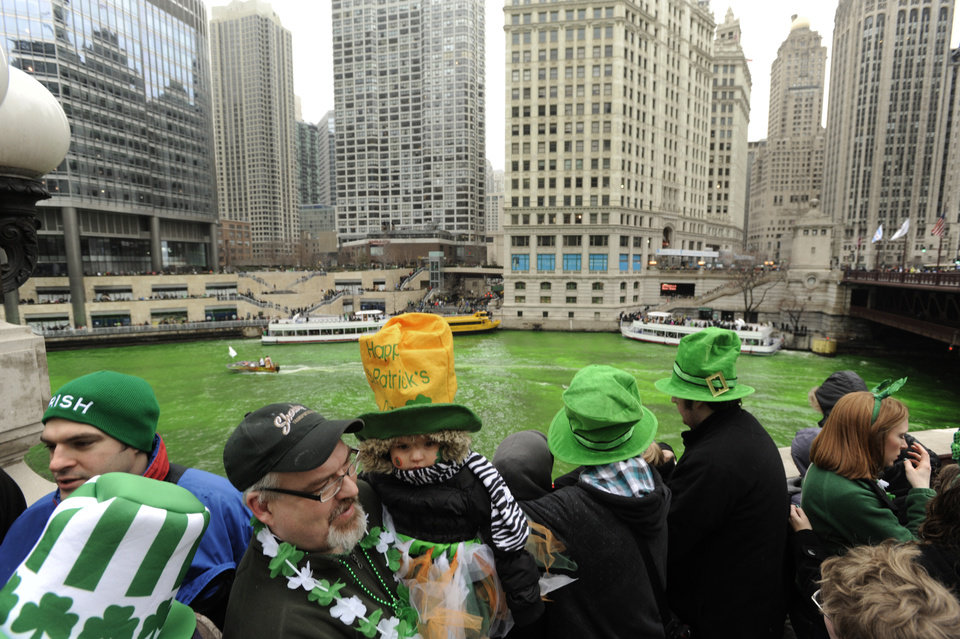 Photo - Spectators watch as the Chicago River is dyed green ahead of the St. Patrick's Day parade in Chicago, Saturday, March, 16, 2013.  With the holiday itself falling on a Sunday, many celebrations were scheduled instead for Saturday because of religious observances. (AP Photo/Paul Beaty)