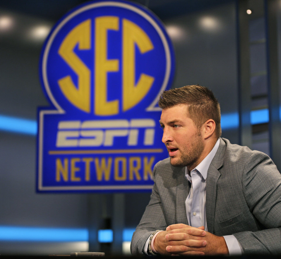 Photo - Tim Tebow answers a question during an interview on the set of ESPN's new SEC Network in Charlotte, N.C., Wednesday, Aug. 6, 2014. Tebow has a new job as a commentator for the SEC Network, but is still looking for work in the NFL as a quarterback. (AP Photo/Chuck Burton)