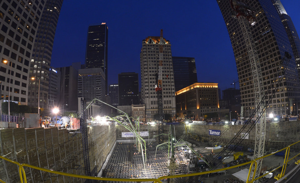Photo - In this photo made with a fisheye lens, crews pour concrete to lay the foundation for the New Wilshire Grand building in a record attempt for the largest continuous concrete pour in history, Saturday, Feb. 15, 2014, in downtown Los Angeles. The marathon pour is expected to last 20 hours without interruption. The attempt will be verified by an official from Guinness World Records.  The New Wilshire Grand will be the tallest building to be built west of the Mississippi and is expected to be completed in 2017. (AP Photo/Mark J. Terrill)